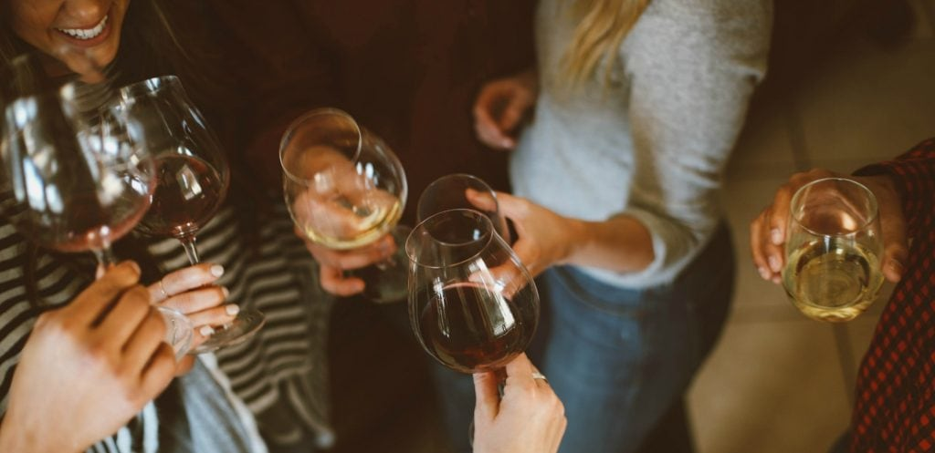 6 wine glasses held by women's hands toast Michigan Wine Trails