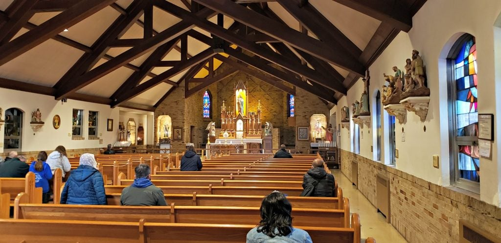 large chapel with pitched ceiling and wooden beams and modern stained glass - people who have come to these Green Bay WI Attractions sit in wood pews