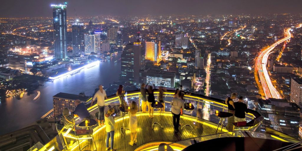 night lights reflect in the river below as people look over glass railing at Sky Bar Bangkok one of the bset rooftop bars in Bangkok