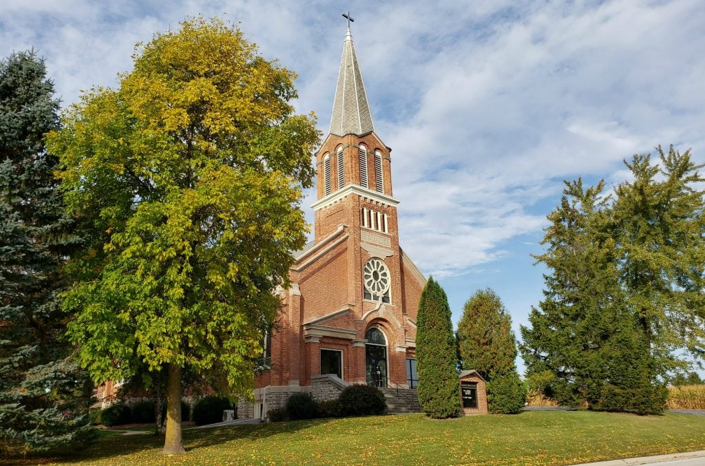 red brick church with tall steeple and rose window at St James Catholic Church Cooperstown
