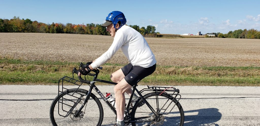 older man in helmet on mountain bike with farm fields behind him and barn with silo on horizon on Wisc Way