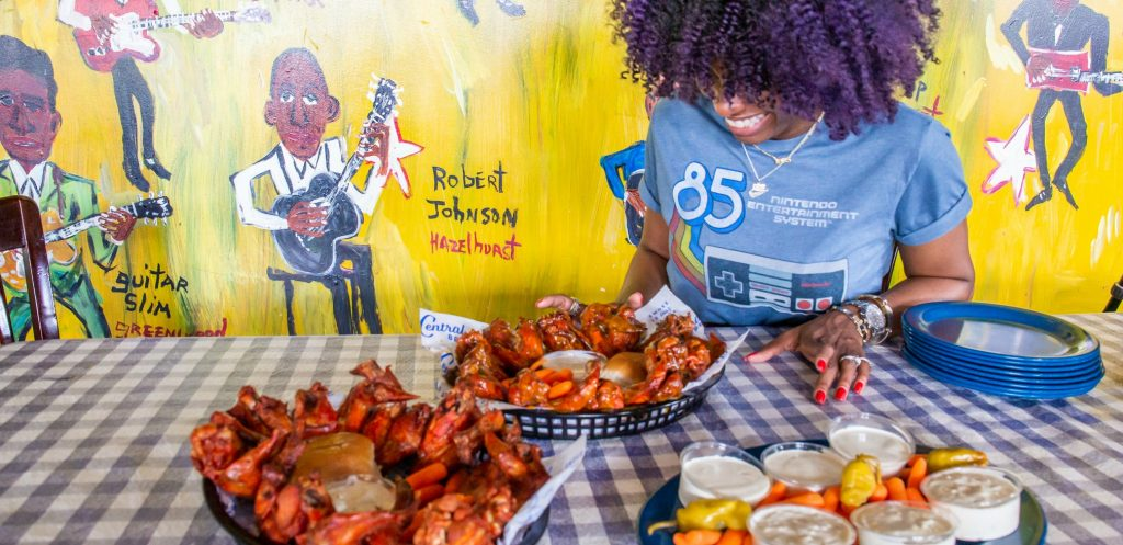 woman looks down at two platters of hot wings - wall of colorful primitive painting behind