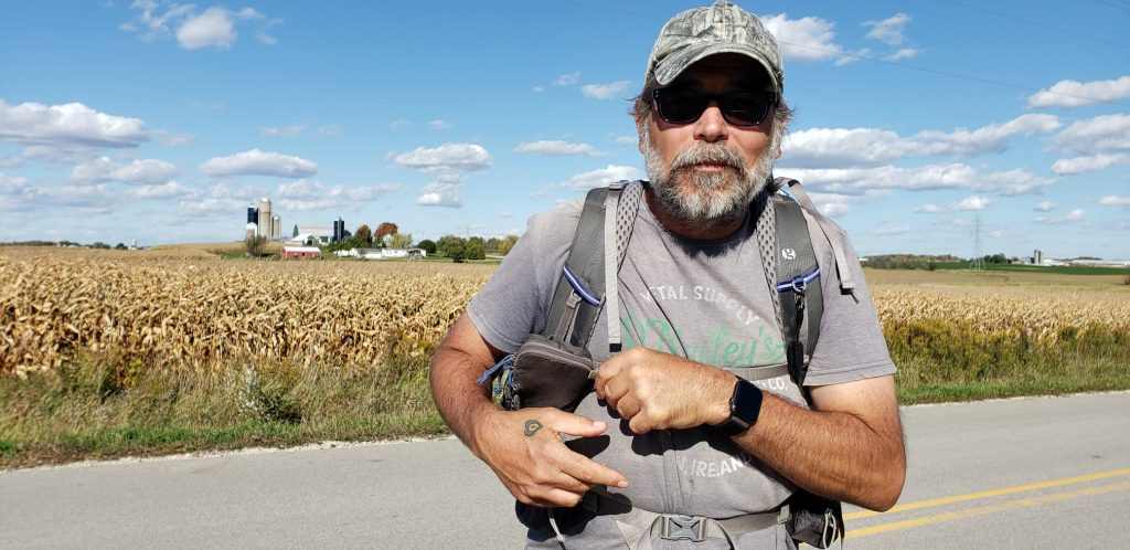 bearded man with sunglasses looks at camera on the Wisconsin pilgrimage