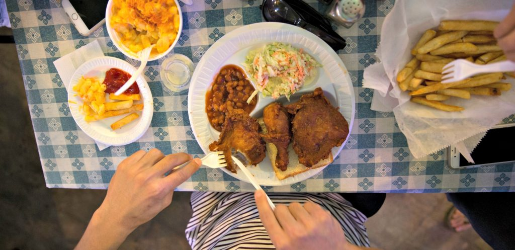photo looking down at table with blue checked table cloth, plate of southern food and hands cutting the breaded fried meat some of the bset food in memphis, of course!