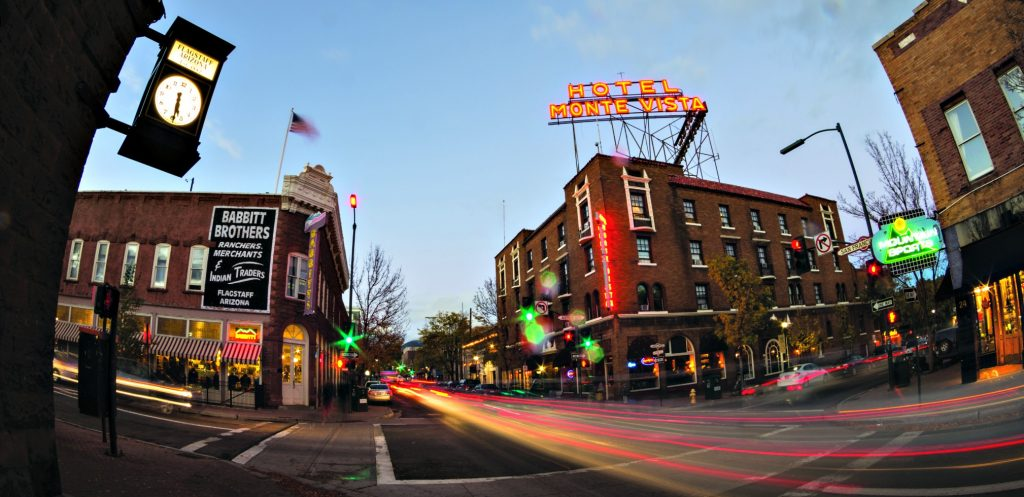 wide angle view of downtown Flagstaff at dusk with neon lights stop Hotel Monte V an Babbitt Trading Co