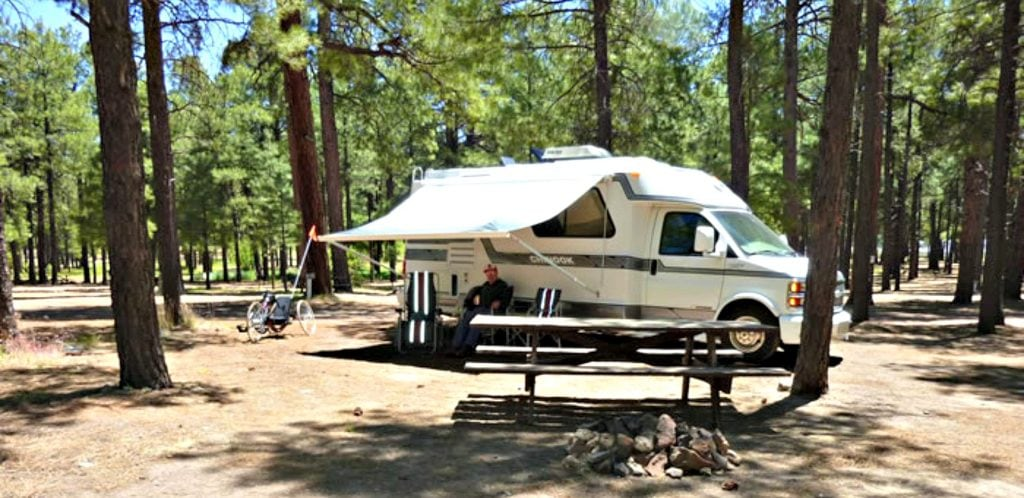 Camping van at Fort Tuthill Campground with campfire ring in front and Ponderosa pines in the background, a fun thing to do in Flagstaff