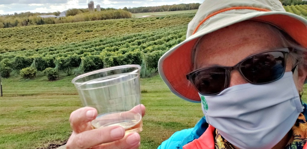 unstoppable stacey in mask holds wine glass with green Parallel 44 winery vineyards behind