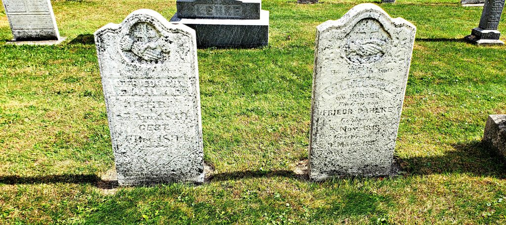 two old worn headstones reveal birthdates of 1819 and 1818