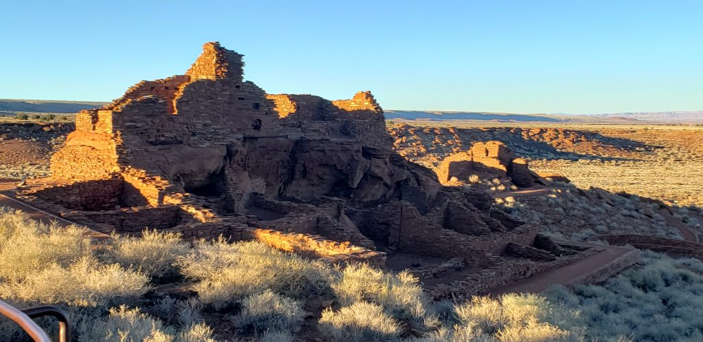 three story ruins made of red rock are bathe in evening low light