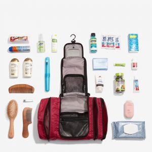 hanging travel organizers lies open on flat surface with travel toiletries arranges around it