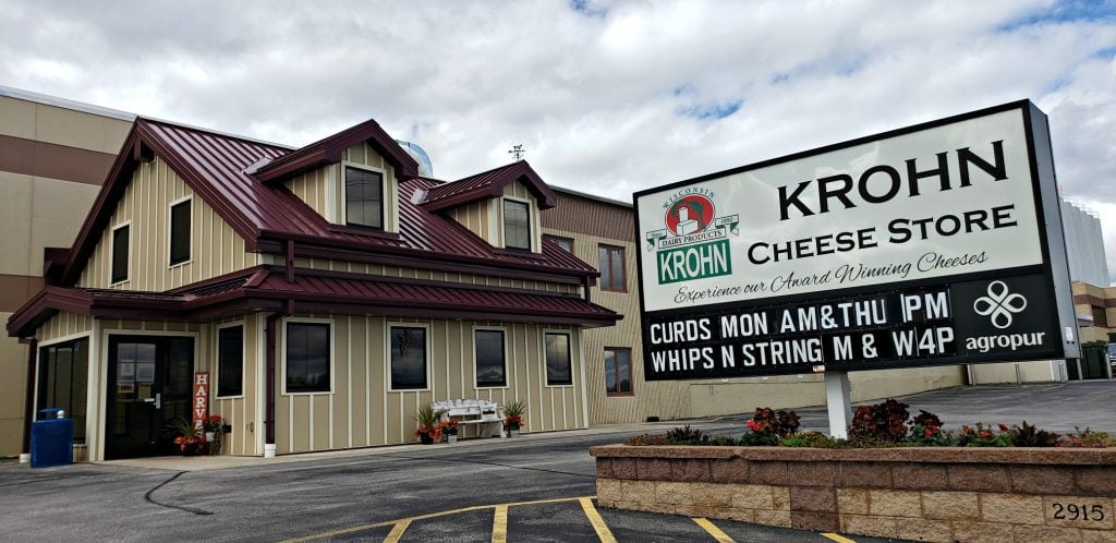 """sign in front of cheese shop reads """" Krohn Cheese Store- curds, whips n strings"""" on Wisc Way pilgrimage"""
