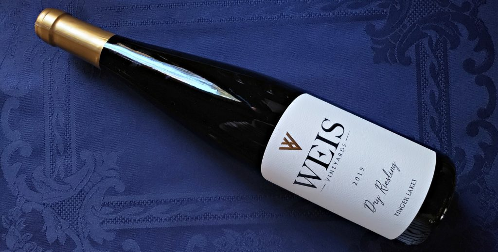 bottle of Weis Dry Riesling, 2019Weis Dry Riesling lies diagonally on regal blue mat with elegant white label and gold capsule