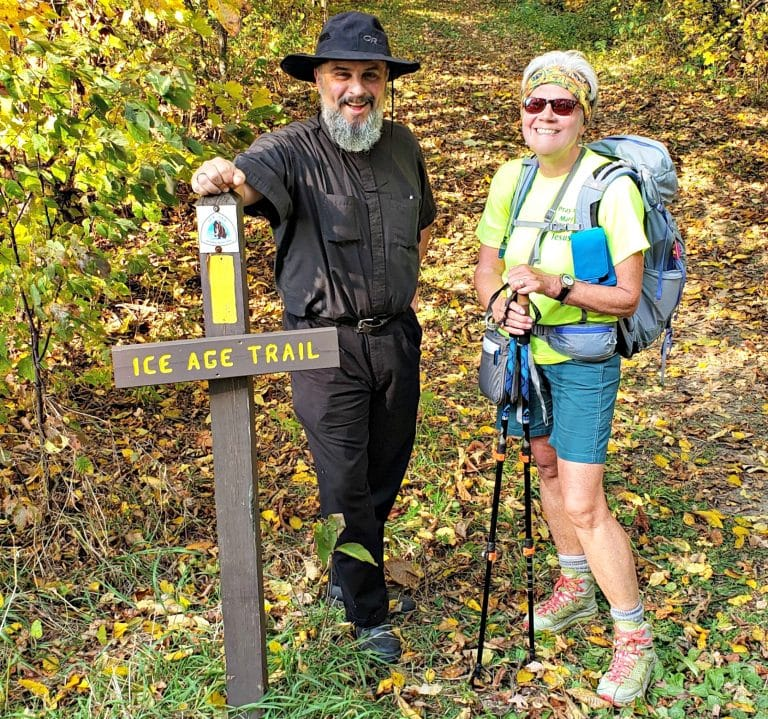 man in floppy black hiking hat and black clothes stands next to author with backpack next to sign reading Ice Age Trail