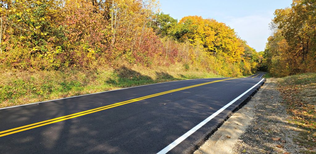 Fresh yellow and white road stripes on black asphalt road makes a pleasant picture as it rolls through thich forest decked in fall colors