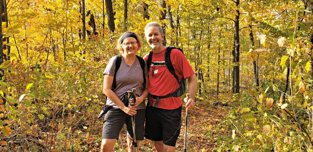 Woman with hiking poles and man with daypack stand together smiling while hiking Kettle Moraine State Forest