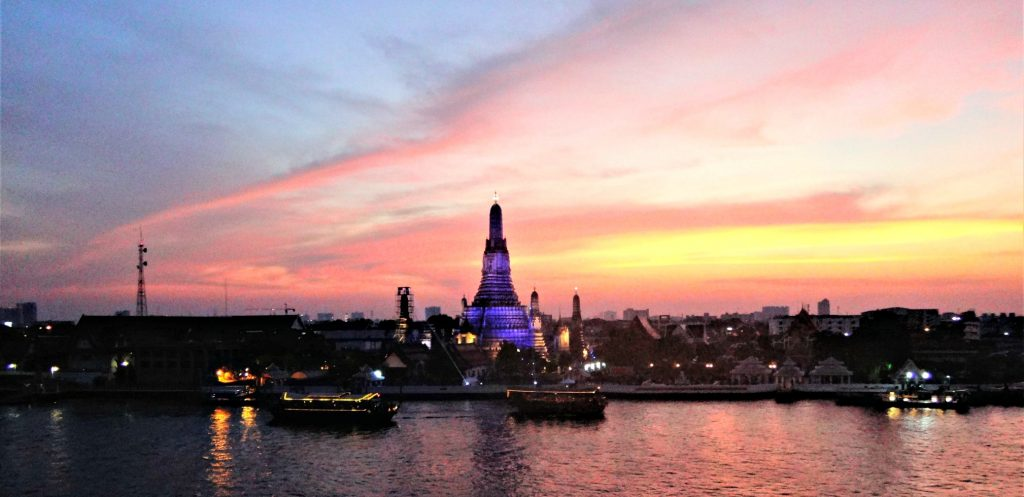 brilliant sun set over a Thai temple is reflected from the river in front of the rooftop bar in Bangkok