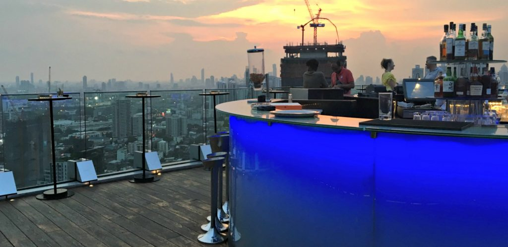 bar is supported by blue backlit footings on top of one of the rooftop bars in Bangkok - the city can be seen below