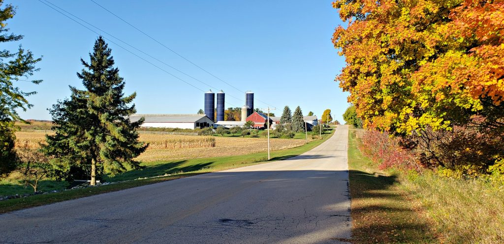 farm with 3 tall silos on top of hill with county road stretching to it on the Wisconsin pilgrimage