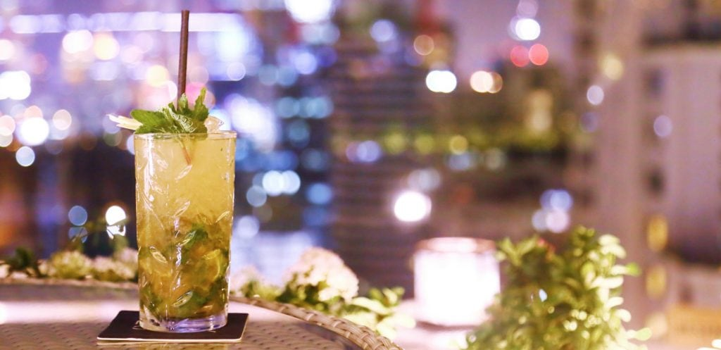 close up of drink in tall glass with brown straw on woven matt with lights of the city night dazzling behind at one of the best rooftop bars bangkok
