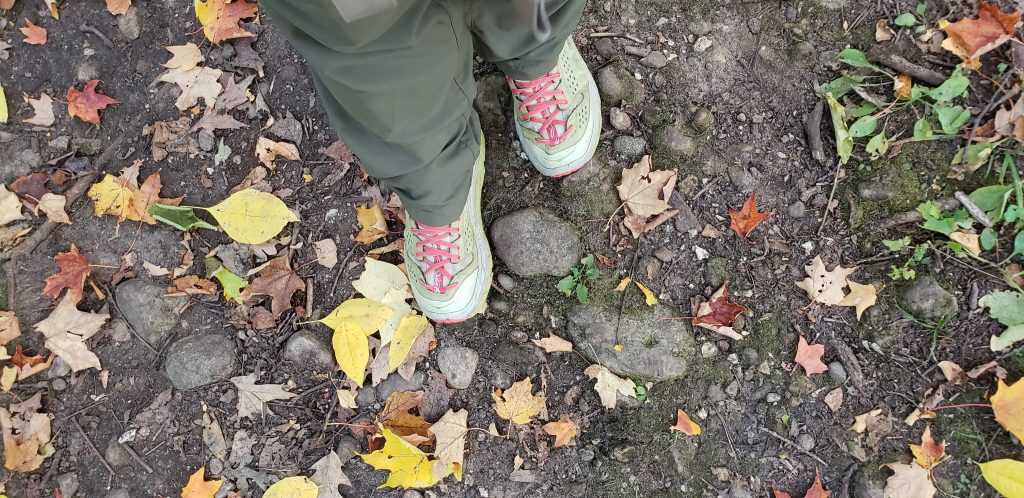 UNSTOPPABLE STacey's feet and hiking boots on rocky trail with yellow and red leaves fallen in path