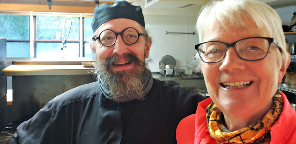 man in black cap and round-rimmed glasses and beard smiles as woman with glasses in orange shirt takes selfie with him at Holy Resurrection Monastery
