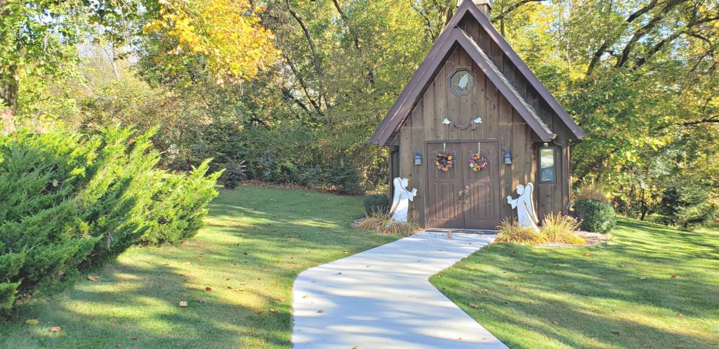 concrete path winds to dark wood sided chapel, one of the Catholic Shrines in Wisconsin