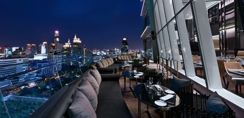 side of building cantilevers over balcony bar gives sense of vertigo bangkok while the dark sky enhances the night lights of the city below