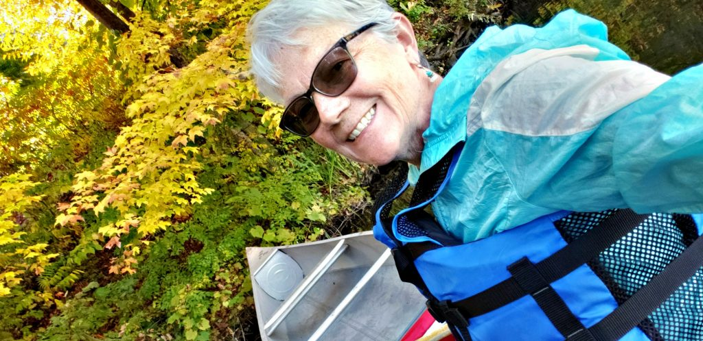 author with sunglasses smiles at camera while sitting in canoe with fall colors behind