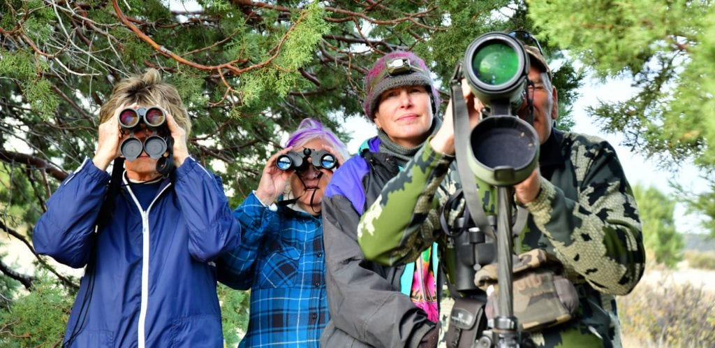 4 people stand facing the viewer while looking through binoculars or viewing scope at Arizona animals - green juniper trees behind