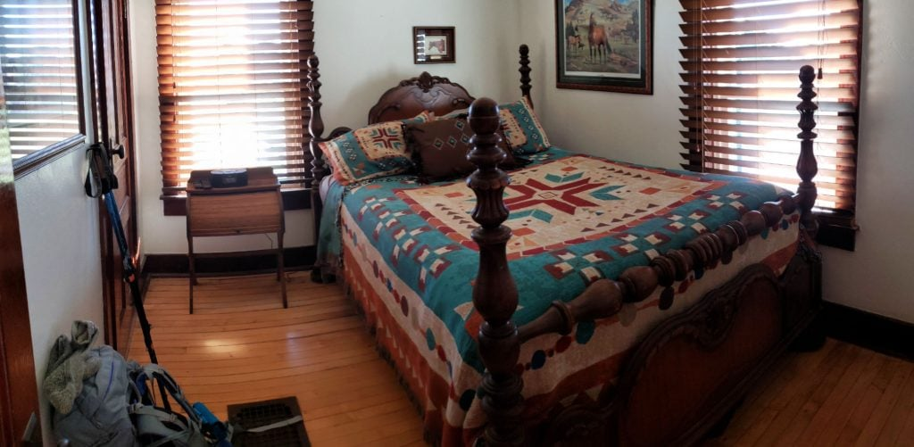 four-posted bed, wood floor, two windows and turquoise quilt at Stacey's bedroom at Paluso Guest Ranch