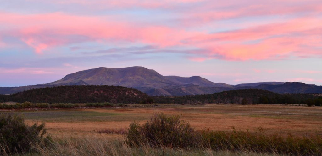 cotton candy pink sky over a hump of mountain and grassy prairie in foreground at the Arizona wildlife viewing area