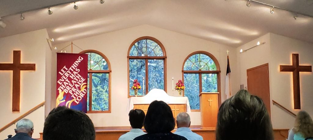 church altar with communion elements shrouded with white cloth- three tall, arched windows are behind with green and yellows trees showing through the glass panes