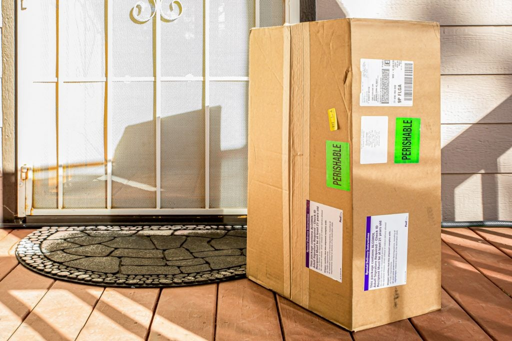 Huge cardboard shipping box sits at door step with colorful labels