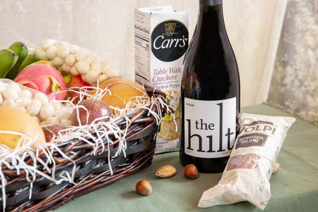 a box of crackers, bottle of Pinot Noir and package of salami sit next to Melissa's Produce gift basket