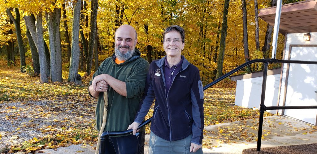 a man holding a hiking stick and a woman stand in front of church with fall colors in the background