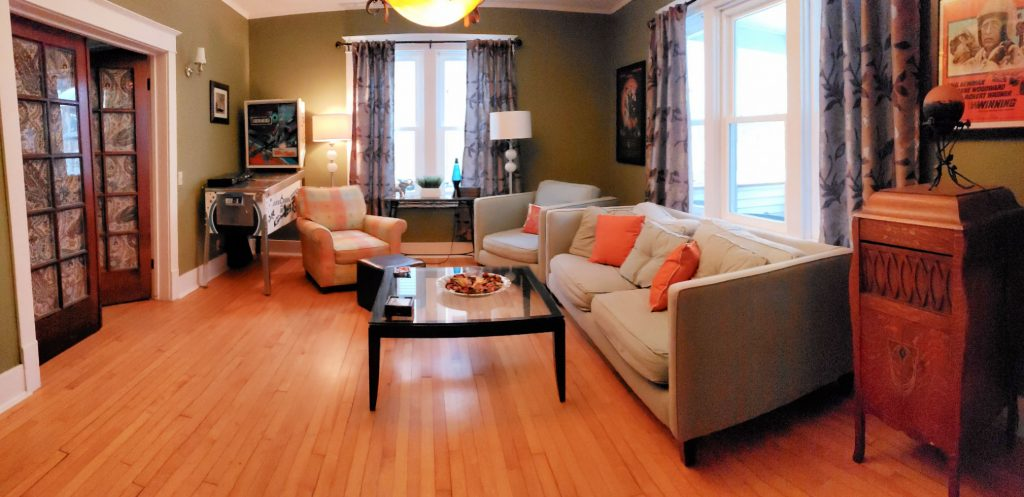 sitting room in this Elkhart Lake lodging has eclectic design including midcentury modern couches with orange pillow, hardwood floor, original dark woodwork, modern green walls