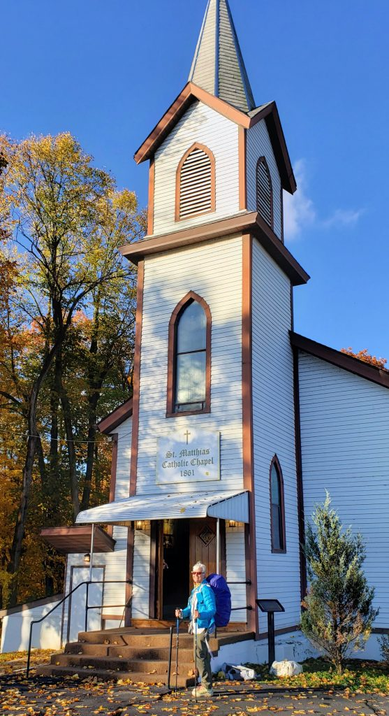 Woman with backpack stands next tto tall white church with steeple on her zero-day
