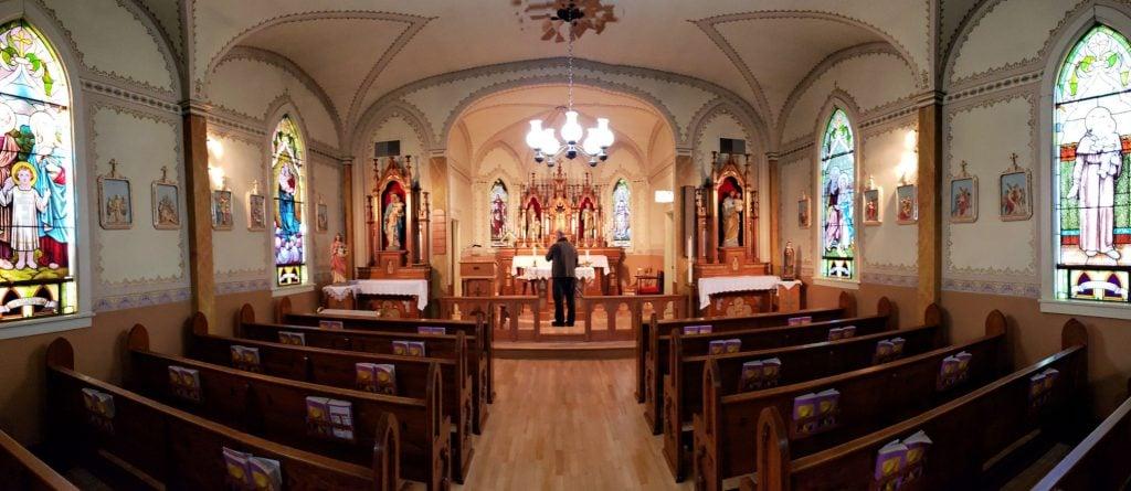 Man is dark clothing stands at dimly lit altar, pews in foreground, interior of saint Matthias Catholic church