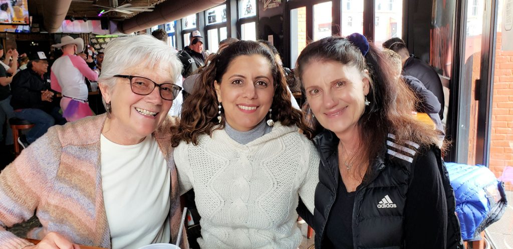 3 women with arms around each other sit at table while travelling to Nashville