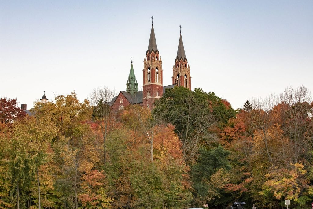 twin spires of a church rise above the forest in golden fall colors at Holy Hill Church Wisconsin where the way is made by walking