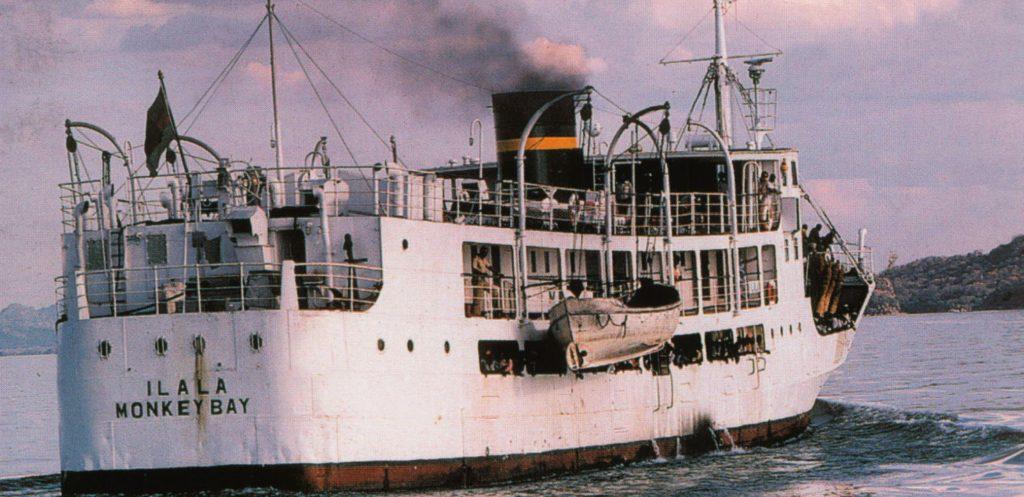 white sided ship with black smoke stack steams up lake Malawi