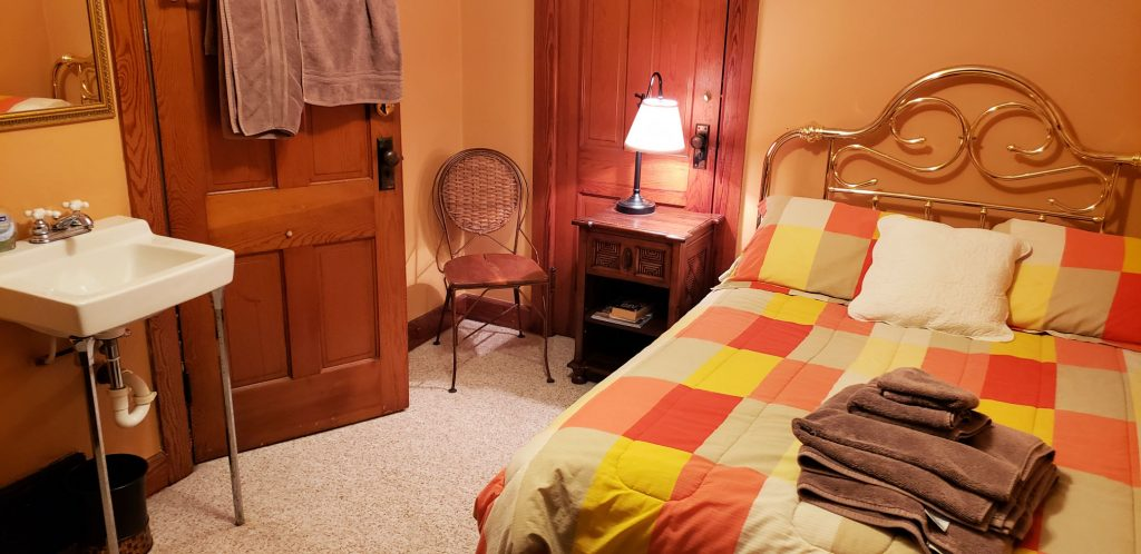 bed with comforter of orange, cantaloupe and lemon colors, in-room sink and wood doors