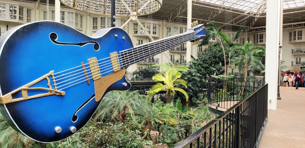 huge blue electric guitar hangs from ceiling with tropical garden below in atrium in Nashville now