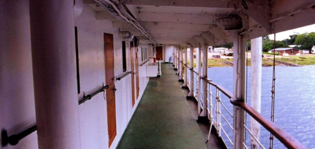 looking down bridge deck with cabin doors to the left and open balcony to right