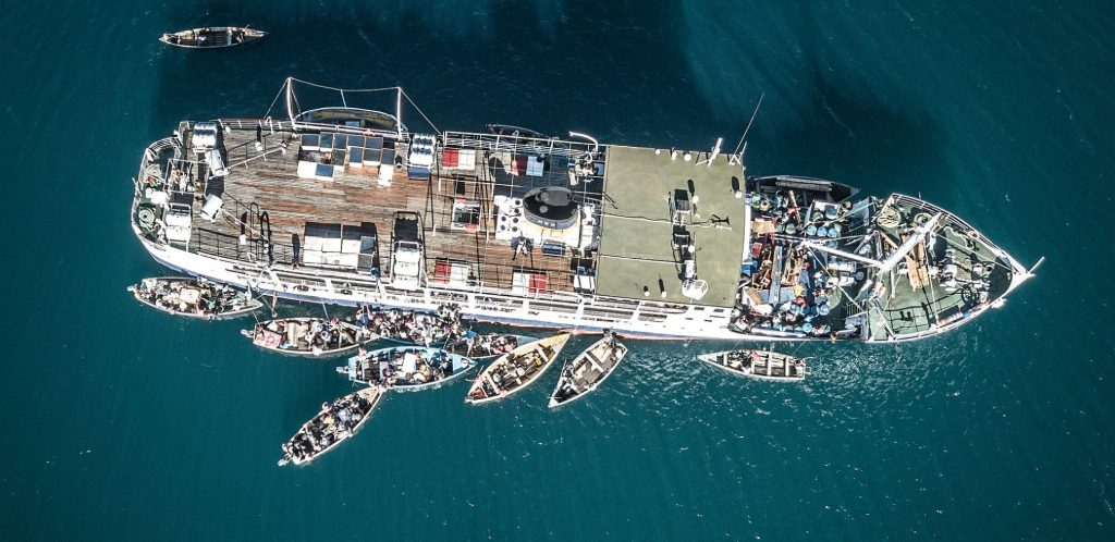 birds eye view of Ilana ferry Malawi surrounded by merchant boats on Malawi Lake which is deep teal in color