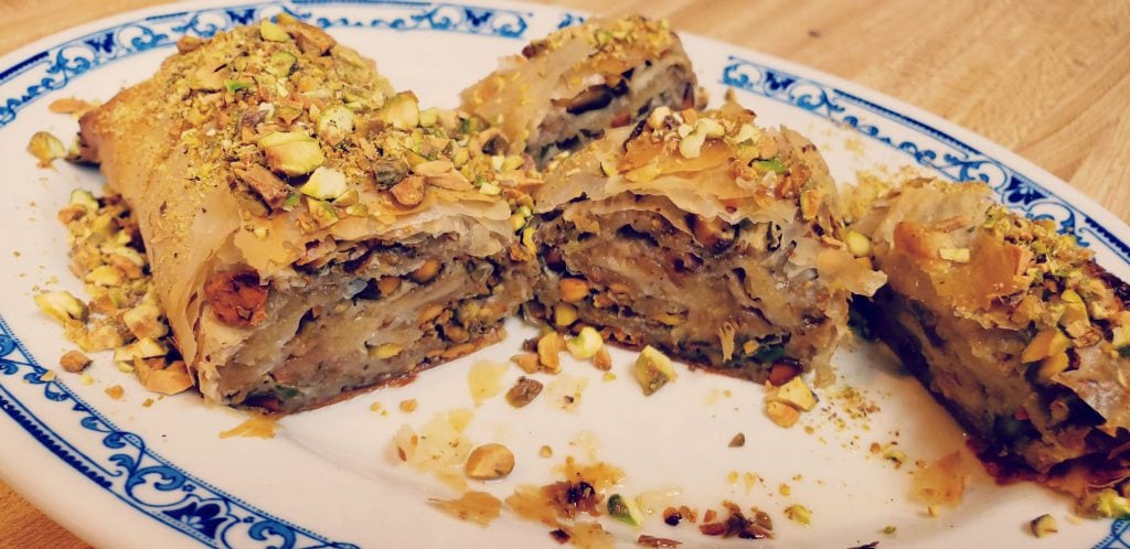 feijoa strudel on plate cut in three pieces - pistachios sprinkled around