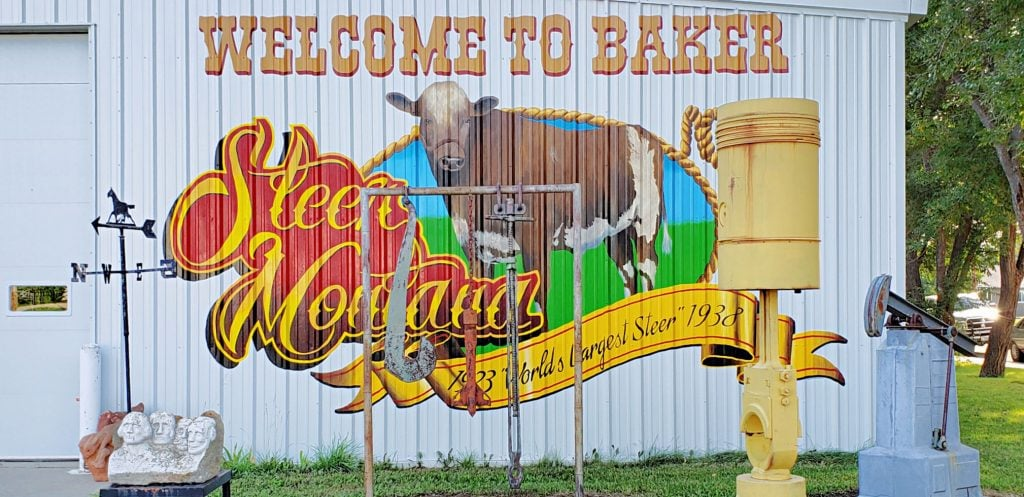 """sign painted on side of metal buildin reads: """"Welcome to Baker - World's largest steer"""""""