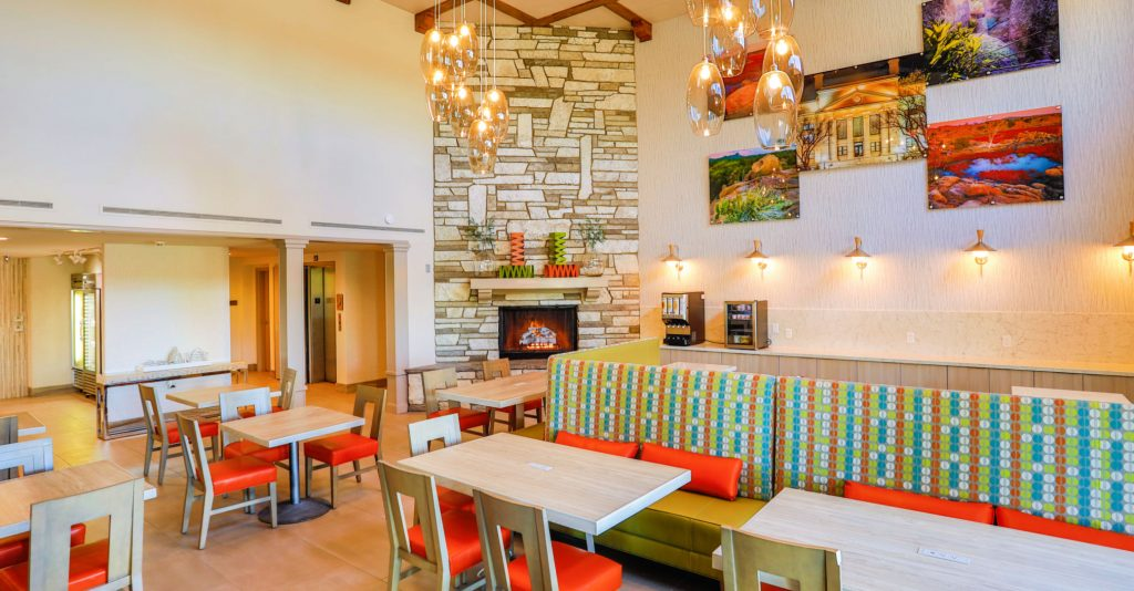 Two-story open room with fireplace, modern lighting fixtures and bright orange chairs at tables
