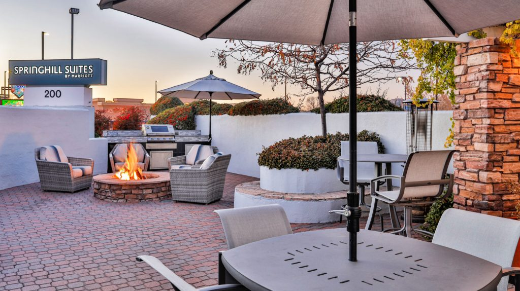 outdoor patio with gas grill, firepit, comfy deep chairs, umbrella tables and tile flooring