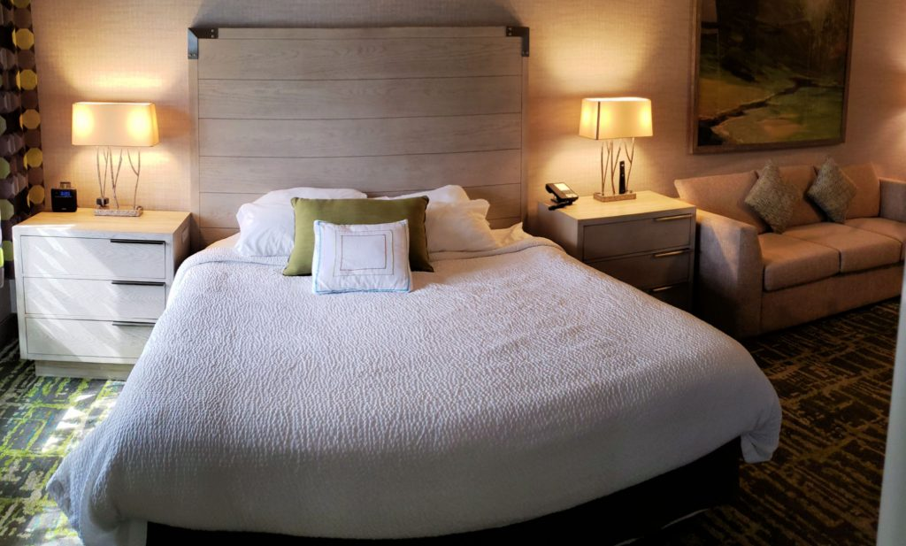 king bed in white comforter with two contemporary side tables/dressers with three drawers each